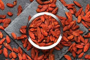 Dried red goji berries on gray backg