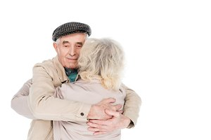 cheerful retired man hugging wife is