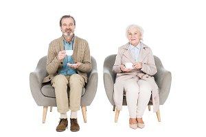 happy senior couple holding cups wit