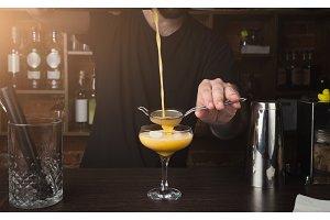 Hands of barman preparing cocktail