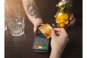 Woman paying for cocktail with