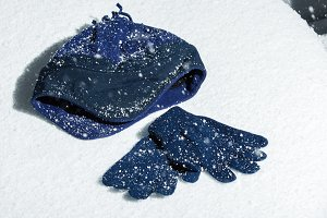 Blue knit cap and gloves on snow