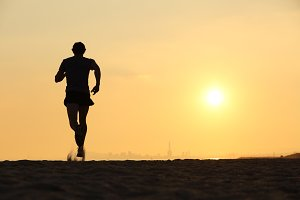 Back view of a man running on the beach at sunset.jpg