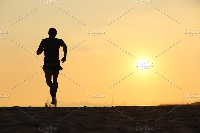 Back view of a man running on the beach at sunset.jpg - Sports