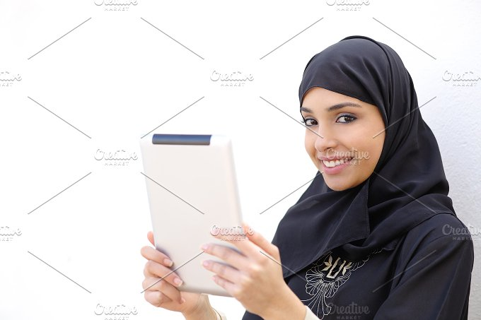 Arab woman holding a tablet and looking at camera.jpg - Technology