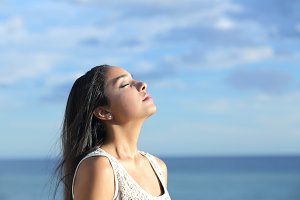 Beautiful arab woman breathing fresh air in the beach.jpg