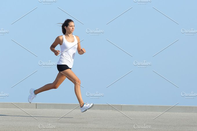 Beautiful sportswoman running with the sky in the background.jpg - Sports