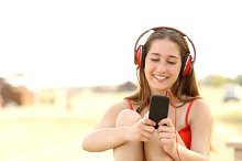 Candid teen girl listening to the music from a smart phone.jpg
