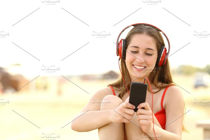Candid teen girl listening to the music from a smart phone.jpg - Technology