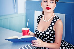 Pin up girl with book in cafe