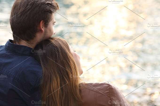 Couple hugging and watching sunset on the beach.jpg - People