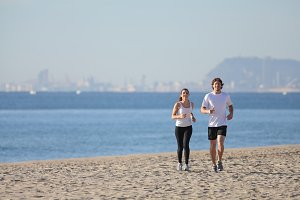 Couple running on the beach with Barcelona in the background.jpg