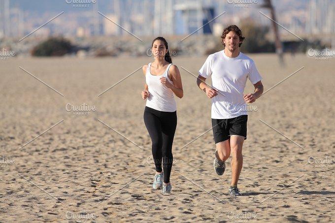 Couple running on the beach.jpg - Sports