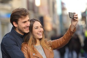 Couple taking selfie photo with a smart phone in the street.jpg