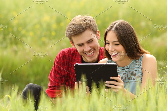Couple watching videos in a tablet in a field.jpg - Technology