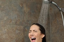 Disgusted woman screaming in the shower under cold water.jpg