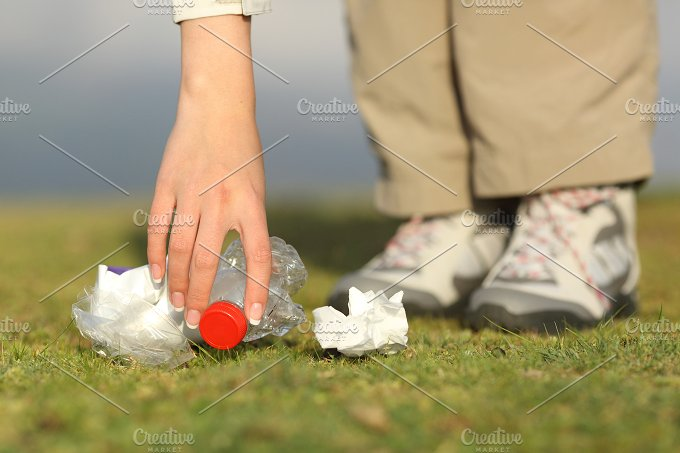 Eco hiker hand collecting garbage in the mountain.jpg - Nature