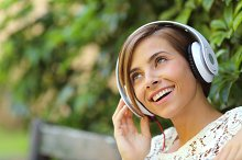 Girl listening to the music with headphones in a park.jpg