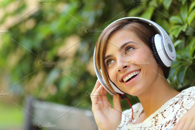 Girl listening to the music with headphones in a park.jpg - Technology