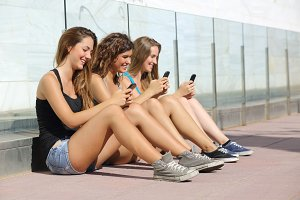 Group of teenager girls smiling happy texting on the smart phone.jpg
