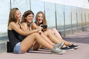 Group of three teenager girls sitting on the floor laughing while watching the smart phone.jpg