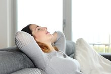 Happy relaxed woman resting on a couch at home.jpg