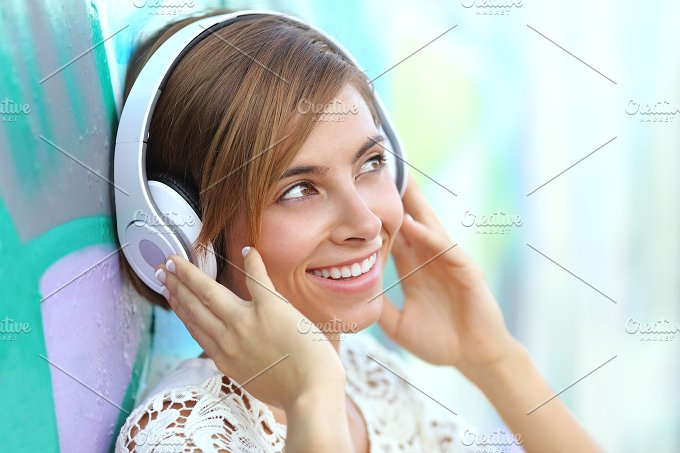 Happy woman with headphones listening to the music.jpg - Technology