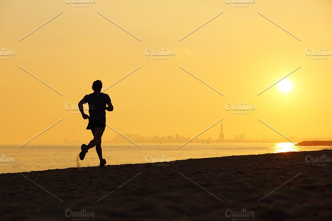 Jogger silhouette running on the beach at sunset.jpg - Sports