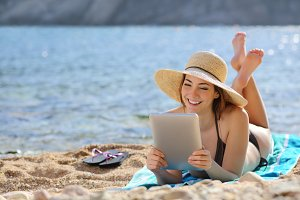 Pretty woman reading a tablet reader on the beach on vacations.jpg