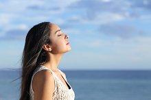 Profile of a beautiful arab woman breathing fresh air in the beach.jpg