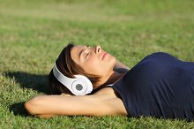 Relaxed woman listening to the music with headphones lying on the grass.jpg