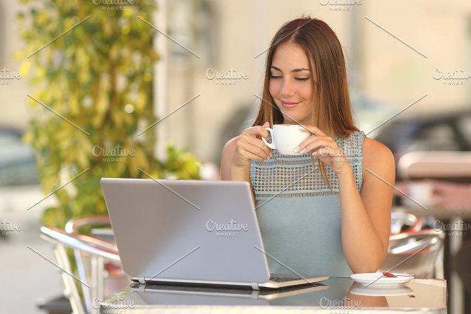 Relaxed woman watching a laptop in a restaurant.jpg - Technology
