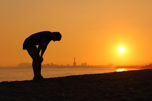 Silhouette of an tired sportsman at sunset.jpg