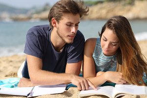Teenager couple or friends students studying on the beach.jpg