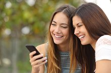 Two happy women friends sharing a smart phone.jpg