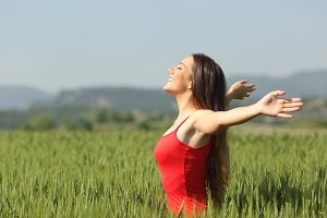 Woman breathing deep fresh air in a field.jpg