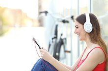 Woman listening to the music from a tablet in a park.jpg