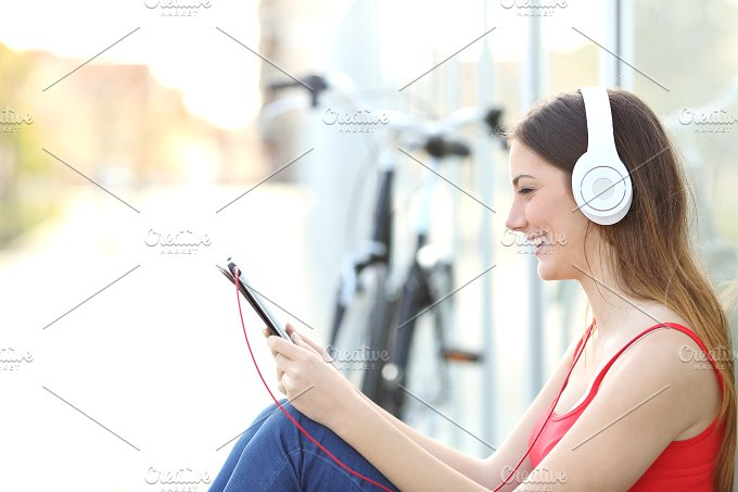 Woman listening to the music from a tablet in a park.jpg - Technology