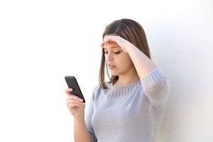 Worried woman looking at the mobile phone.jpg