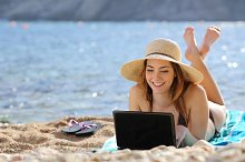 Woman on the beach browsing social media on a computer in summer.jpg