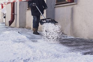 adult man shoveling snow from city s