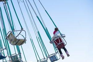 child having fun riding on a chain c