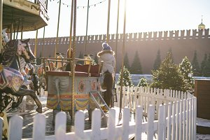 photo of colorful carousel with chil