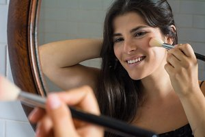 Woman applying make up in bathroom.