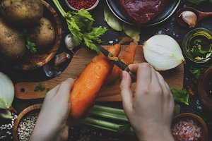 Womens hands are cleaning carrots. C