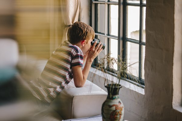 People Images: Jacob Lund - Curious boy looking out the window