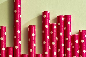 Red drinking straws on white points.