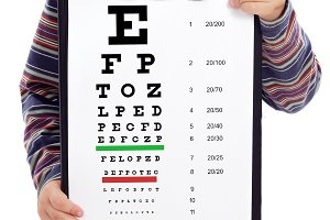 Child holding a vision exam chart