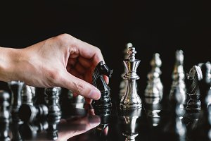 hand of businessman moving chess