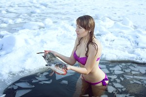 Girl with fish stands in the ice-hol